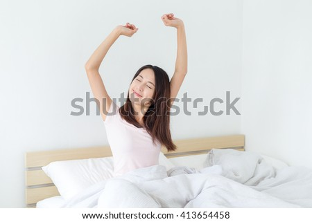 Woman stretching in bed at home  - stock photo