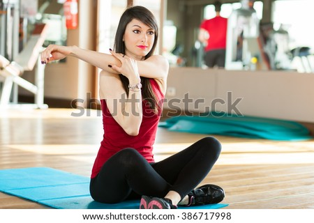 Woman stretching in the gym - stock photo
