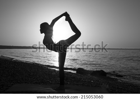 Woman stretching in yoga exercise fitness training at coastline at sunset, monochrome image
