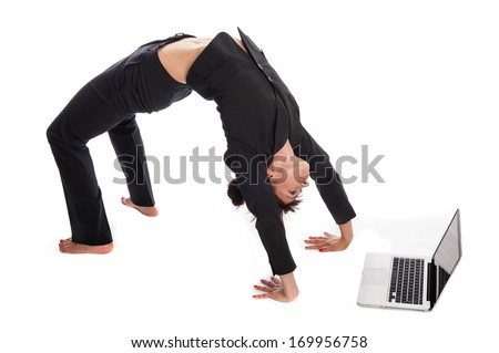 Woman stretching in yoga pose whilst working on a laptop. Isolated on white. - stock photo