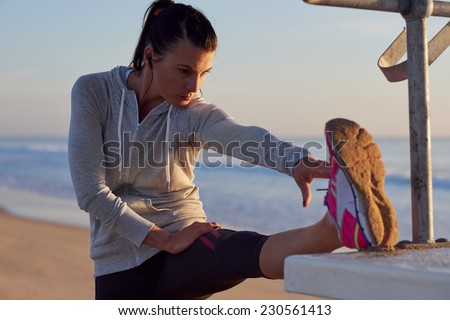 woman stretching leg muscle before early morning run workout on beach