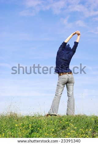 woman stretching on a grass hill - stock photo
