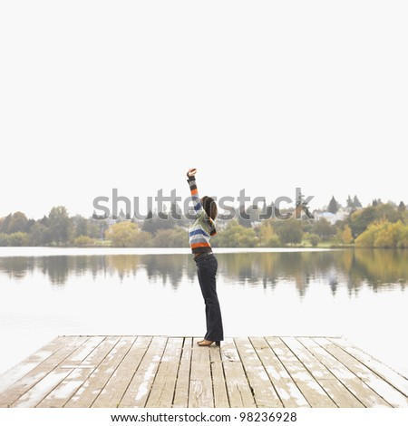 Woman stretching on dock - stock photo