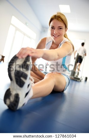 Woman stretching out in gym center - stock photo