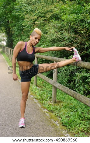 Woman stretching outdoors - stock photo