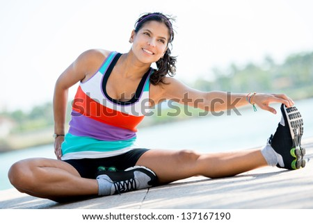 Woman stretching outdoors before starting her workout - stock photo