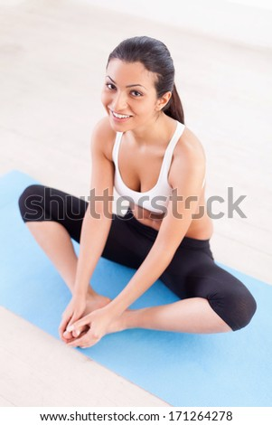 Woman stretching. Top view of cheerful young Indian woman warming up before training