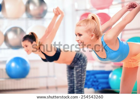 Woman stretching. Two beautiful young women in sports clothing exercising together and smiling while standing against fit ball rows in sports club