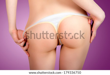 Woman stripping off thong and showing her backside - stock photo