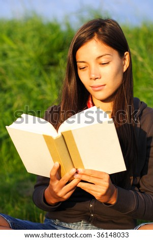 Woman student reading book in warm evening light.