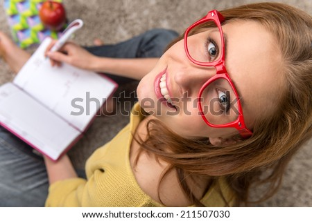 Woman student sitting thinking while studying. top view of pretty girl making note in textbook - stock photo