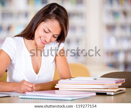 Woman studying at the library looking happy - stock photo