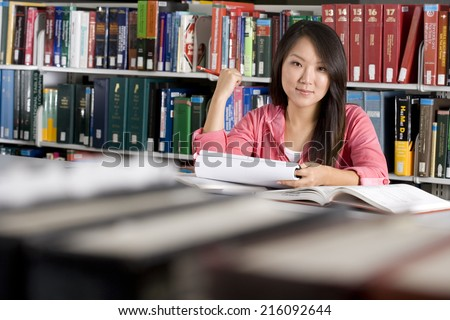 Woman studying in library, smiling, portrait - stock photo