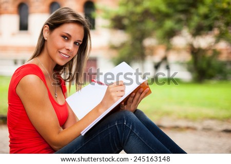 Woman studying while sitting outdoors - stock photo