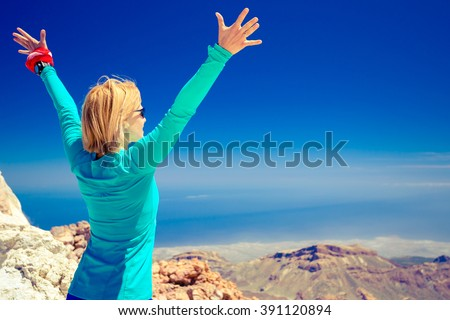 Woman successful hiking climbing in inspirational mountains landscape, beautiful view and ocean. Female hiker with arms up outstretched on mountain top. - stock photo