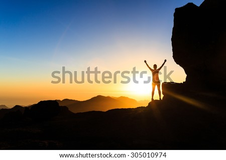 Woman successful hiking climbing silhouette in mountains, motivation and inspiration in beautiful sunset and ocean. Climber arms up outstretched on mountain top looking at inspirational landscape. - stock photo