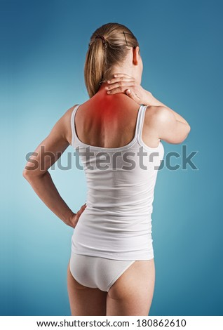 Woman suffer from neck pain, over blue background. Portrait of young girl touching her sick  nape.  - stock photo