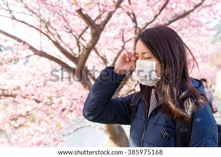 Woman suffer from Pollen allergy under sakura tree - stock photo
