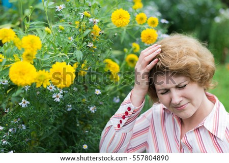Woman suffering from a headache allergic to flowers