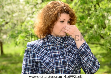 Woman suffering from allergic rhinitis in lush park - stock photo
