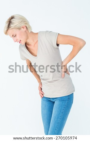 Woman suffering from back pain on white background - stock photo