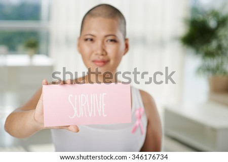 Woman suffering from breast cancer showing plate with survive inscription - stock photo