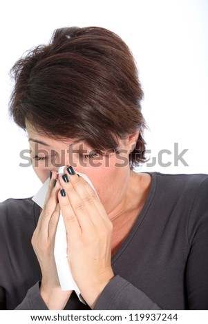 Woman suffering from cold and flu blowing her nose on a handkerchief, head and shoulders studio portrait on white - stock photo