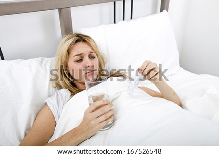 Woman suffering from cold holding water and tablet in bed - stock photo