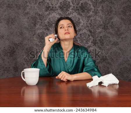 Woman suffering from headache and flu symptoms at home with a coffee cup and tissues taking her temperature