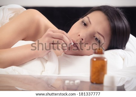 Woman suffering from illness or insomnia lying in bed about to take a tablet from a bottle of medication on the nightstand.