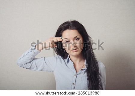 Woman suicide gesture, finger to his temple imitates gun. On a gray background. - stock photo