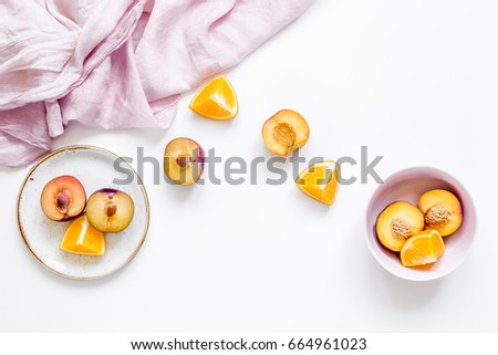 woman summer breackfast with orange and peach fruits and fabric on white background flat lay
