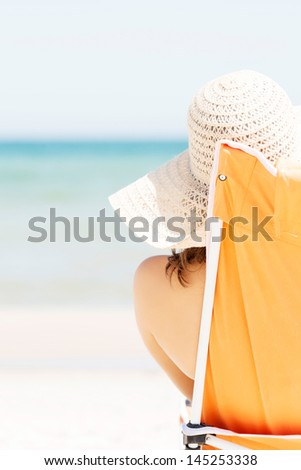 Woman sunbathing and relaxing on beach chair. - stock photo