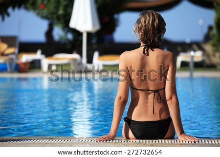 Woman sunbathing by swimming pool. Resort - stock photo