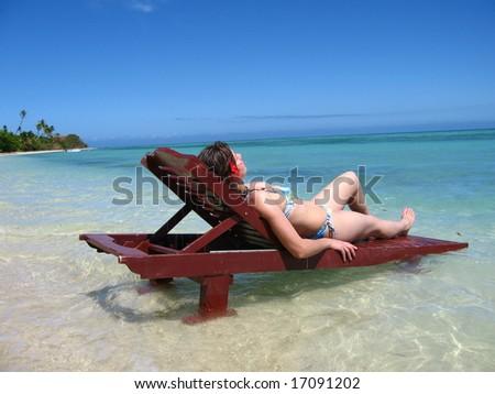 woman sunbathing in a teak chair on a beautiful beach - stock photo