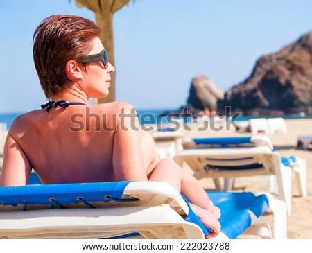 Woman sunbathing in bikini at tropical travel resort. Beautiful young woman lying on sun lounger on a beach - stock photo