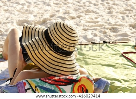 Woman sunbathing on a sandy beach; Florida - stock photo
