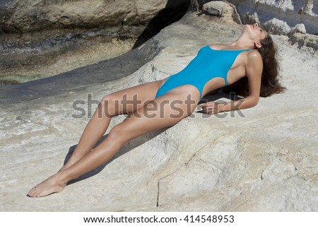 Woman sunbathing on the rocks wearing tight fitting and modish swimsuit.