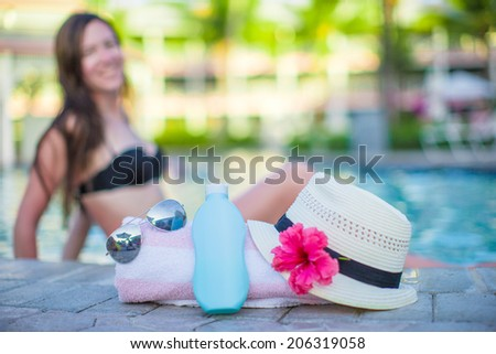 Woman, suncream, hat, sunglasses, flower and tower near swimming pool - stock photo