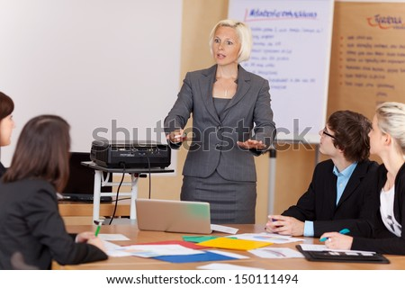 Woman sung a projector giving a corporate training class to a group of young businesspeople around a table gesturing with her hands as she explains something - stock photo