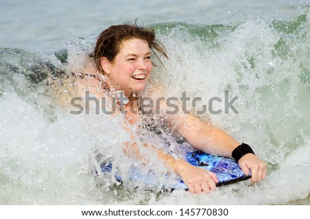 Woman surfing on bodyboard at beach - stock photo