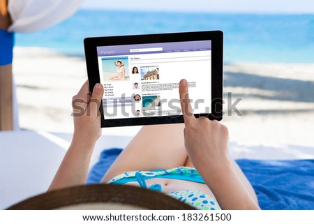 Woman surfing on social site using digital tablet at beach - stock photo