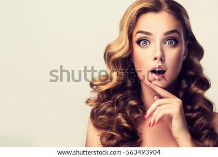 Người phụ nữ cho thấy sản phẩm .Beautiful bất ngờ, ngạc nhiên và cô gái bị sốc bất ngờ với mái tóc xoăn.  Trình bày sản phẩm của bạn.  biểu thức biểu cảm trên khuôn mặt