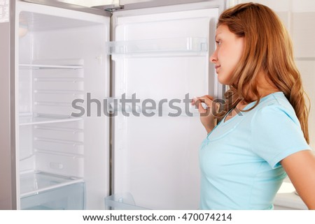 Woman surprised to open door and see an empty refrigerator.
