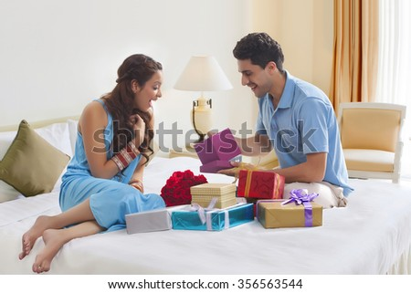 Woman surprised while looking at gift box - stock photo