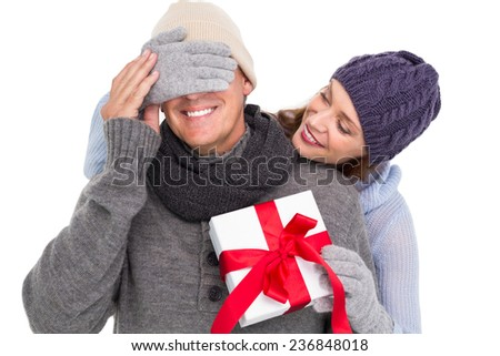 Woman surprising husband with gift on white background
