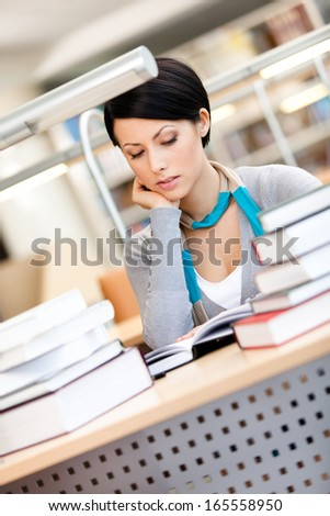 Woman surrounded with piles of books reads sitting at the desk at the library - stock photo