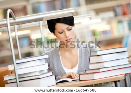 Woman surrounded with piles of books reads sitting at the desk at the library. Information concept - stock photo