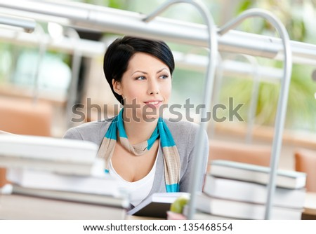 Woman surrounded with piles of books reads sitting at the desk at the library. Learning process - stock photo