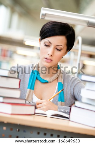 Woman surrounded with piles of books reads sitting at the table at the library. Educational process